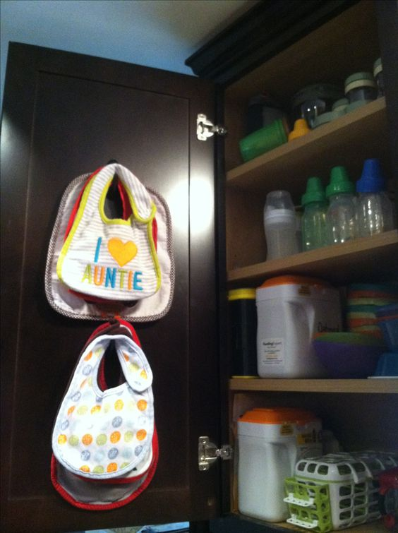 Use command hooks to store bibs inside your kitchen cabinet right there with the bottles and other feeding supplies! This is a genius idea! Check out all of the other awesome ways to organize your little ones bibs at luresandlace.com! #luresandlace