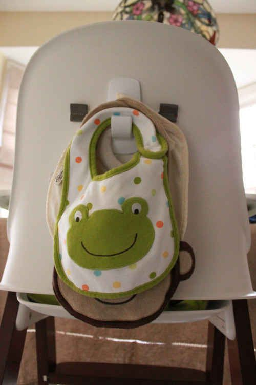 Command hooks are a must have for moms! Stick one on the bsck of the highchair for easy access! Check out all of the other awesome ways to organize your little ones bibs at luresandlace.com! #luresandlace